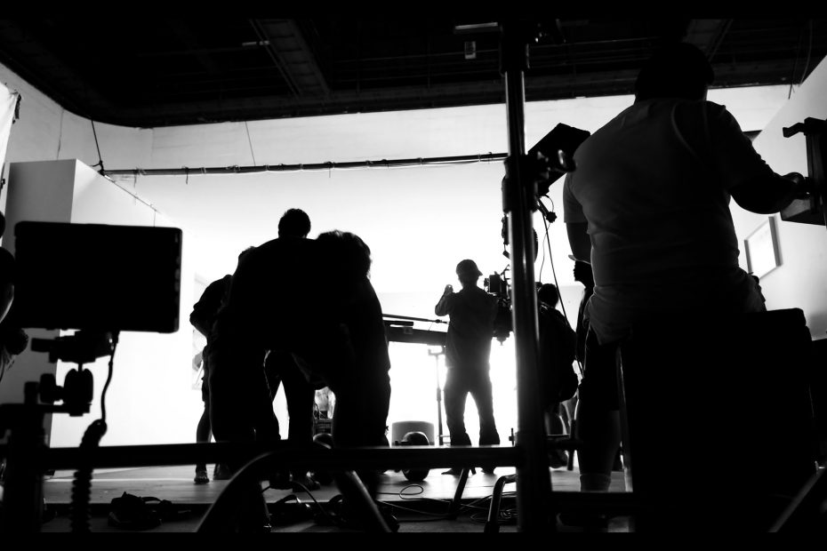 Silhoutte images of video production and lighting set for filming which movie crew team working and