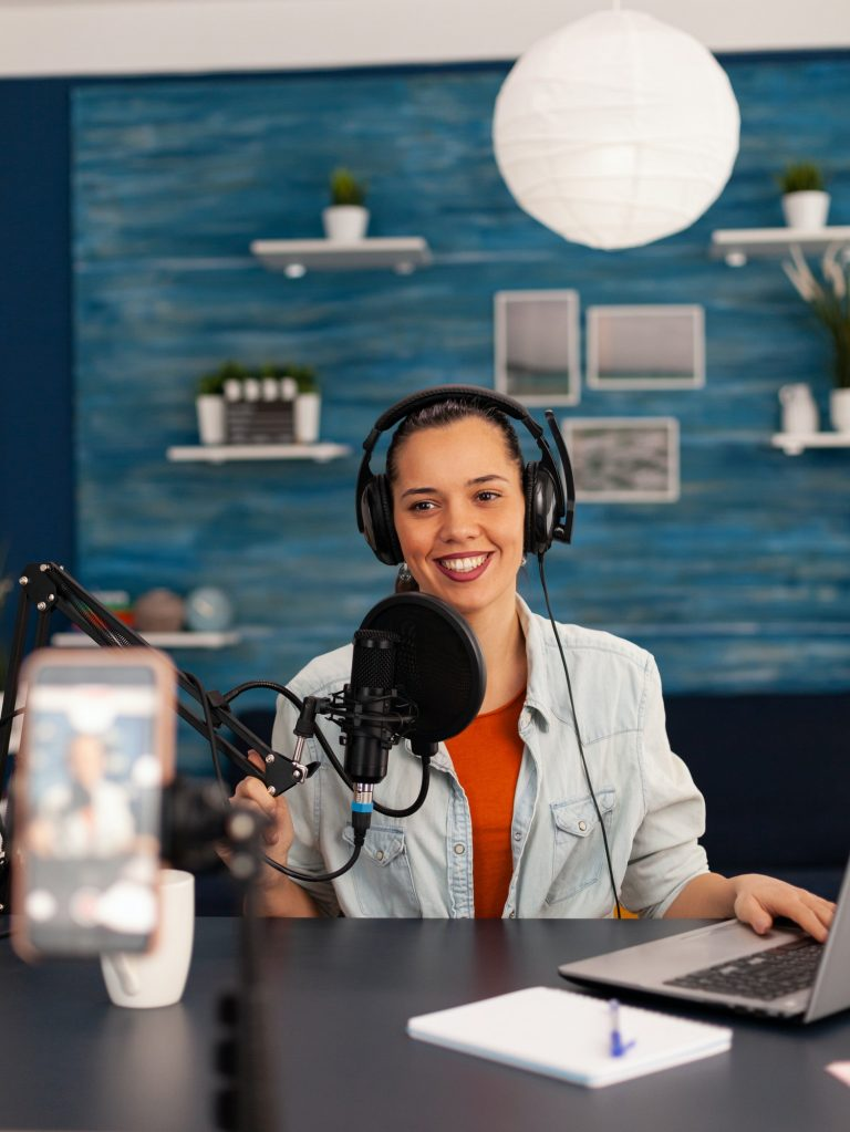 Social media star woman holding professional microphone while recording podcast for youtube channel